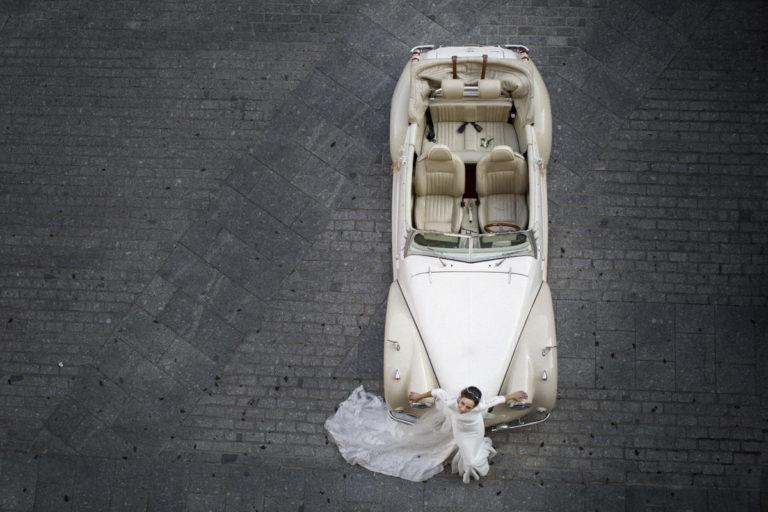 Preciosa imagen de fotografo de bodas Toledo de una novia sobre un descapotable blanco.