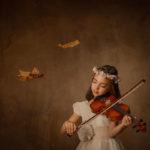 Un fotógrafo toledo haciendo fotos de una niña tocando el violín.